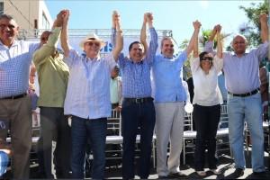 El candidato del PRM, Luis Abinader, junto al renunciante diputado del PLD de Baní, Milcíades Franjul, y otros dirigentes en un acto este domingo.
