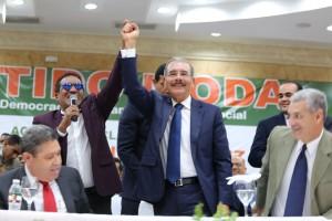El merenguero Kinito Méndez levanta la mayo a Danilo Medina, a manera de proclamación.