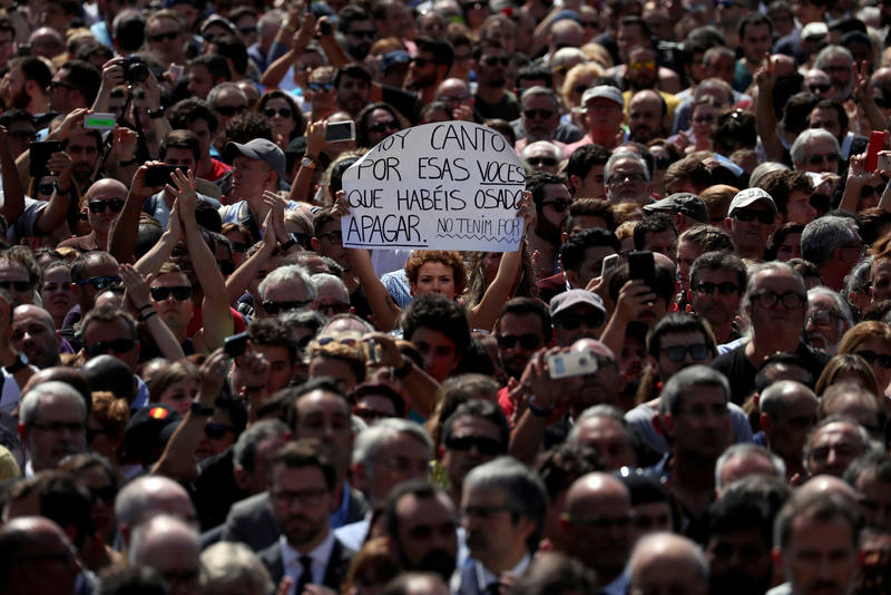 "A woman holds a sign that reads ""I sing today for those voices that you have dared to shut up. We are not afraid"" while observing a minute of silence at Placa de Catalunya, a day after a van crashed into pedestrians at Las Ramblas in Barcelona"